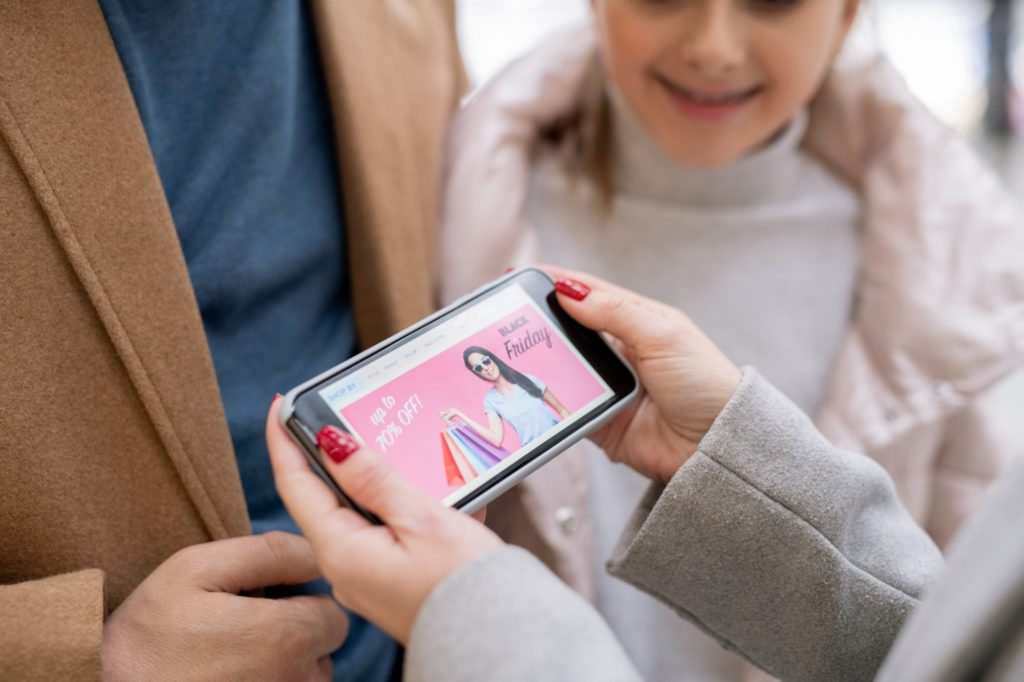 Female hands holding smartphone with home page of online shop